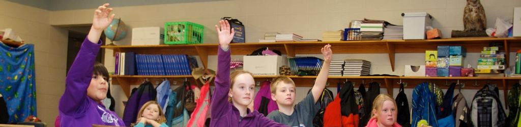 4th graders in class raising hands